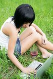Young girl sitting in a park with laptop computer Royalty Free Stock Photography