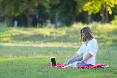 Young girl sitting in the park, smiling and working at his laptop. Stock Image