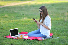 Young girl sitting in the park, smiling and working at his laptop,  listening to music Royalty Free Stock Images