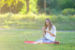 Young girl sitting in the park, smiling and working at his laptop,  listening to music Royalty Free Stock Image
