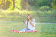 Young girl sitting in the park, smiling and working at his laptop,  listening to music Royalty Free Stock Photo