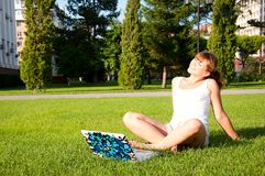 Young girl sitting in the park with your laptop Stock Image