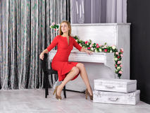 Young girl sitting at piano stock images