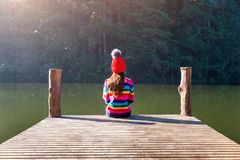 Young girl sitting on a pier.  stock images