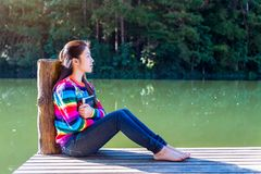 Young girl sitting on a pier. Young girl with a book sitting on a pier stock image