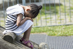 Young girl sitting in a playground with her head in her lap as she is sad. A young girl is in a playground sad Royalty Free Stock Images