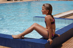 Young girl sitting by the pool Stock Image