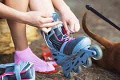 Young girl sitting and putting on inline skates Stock Photography