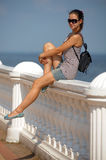 Young girl sitting on the railing. Of the summer Royalty Free Stock Photos