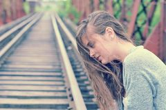Young girl is sitting on the rails for trains in profile royalty free stock photo