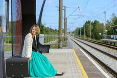Young girl sitting on the railway station Royalty Free Stock Photo