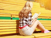 Young girl sitting reading a book on the bench. In city park in summer day Stock Photography