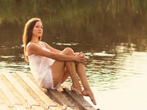 Young girl sitting on the river bank Stock Photo
