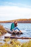 Young girl sitting on the river bank Royalty Free Stock Photo