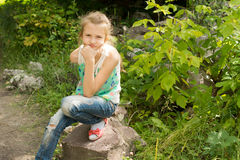 Young girl sitting on a rock thinking Stock Photography