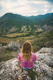 Young girl sitting on a rock stock photography