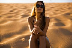 Young girl sitting on a sand dune royalty free stock photography