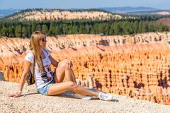 Young girl sitting by the scenic view of stunning red sandstone hoodoos. In Bryce Canyon National Park in Utah, USA royalty free stock photography