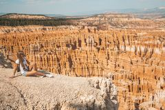 Young girl sitting by the scenic view of stunning red sandstone hoodoos. In Bryce Canyon National Park in Utah, USA stock image