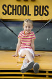 A young girl sitting on a school bus Stock Photo