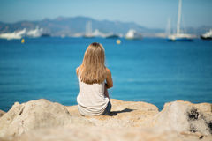 Young girl sitting on the sea shore. In Cannes, France Stock Images