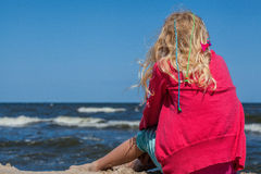 Young girl sitting at shore Stock Photos