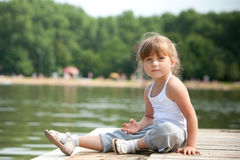 Young girl sitting sitting in a pier Royalty Free Stock Photo
