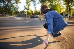Young girl sitting on skateboard. Skateboarding. Outdoors, lifestyle. stock images