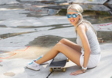 Young girl sitting on skateboard in skatepark Stock Photo