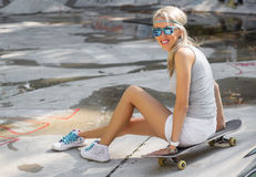 Young girl sitting on skateboard in skatepark Stock Photos