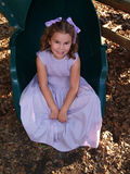 Young Girl Sitting on a Slide royalty free stock image