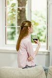 Young girl sitting on sofa, close to open window, holding glass of red wine. Female looking out the window, drinking wine at home Stock Photos