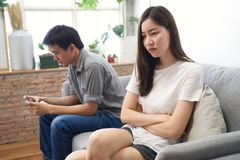 Young girl sitting on sofa is feeling bored with her boyfriend. royalty free stock image