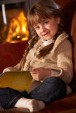 Young Girl Sitting On Sofa And Reading A Book Royalty Free Stock Images