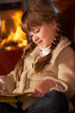 Young Girl Sitting On Sofa Reading A Book. Young Girl Sitting On Sofa And Reading Book By Cosy Log Fire Stock Photo