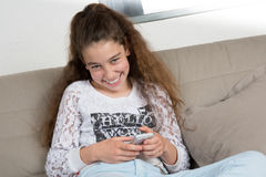 Young girl sitting on a sofa smiling Stock Images