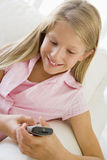 Young Girl Sitting On A Sofa Texting Royalty Free Stock Photos