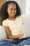 Young Girl Sitting On A Sofa, Using A Laptop Royalty Free Stock Photo