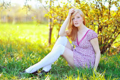 Young girl sitting in a spring blooming garden Stock Photo