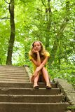 Young girl sitting on the stairs Royalty Free Stock Photography