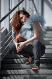 Young girl sitting on the stairs. In a covered walkway Royalty Free Stock Photography