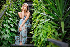 Young girl sitting on the stairs in a garden covered with ivy Stock Photo