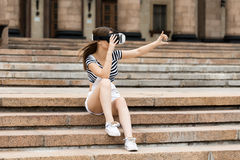 Young girl sitting on the stairs, near the university, is in virtual reality, in VR Stock Photo