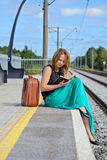 Young girl sitting on the station and reading Royalty Free Stock Photography