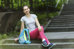 Young  girl sitting on the steps of the alley after a workout. Royalty Free Stock Photos