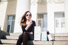 Young girl sitting on the steps with shopping bags. And smartphone in hand Stock Photo