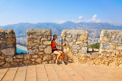 Young girl sitting on the stone. Royalty Free Stock Images