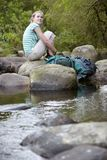 Young Girl Sitting On Stones By Forest Stream Royalty Free Stock Image