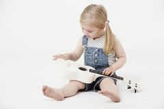 Young girl sitting in studio, playing a guitar Royalty Free Stock Photography