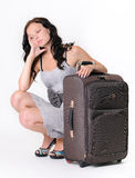 Young girl sitting with a suitcase Stock Photography